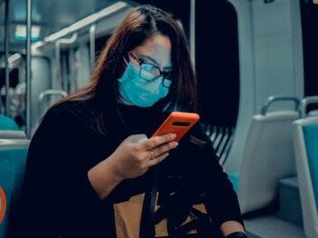 Eine Frau mit OP-Maske sitzt in einer U-Bahn und schaut auf ihr Handy.