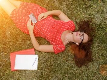 Eine Frau liegt im Gras und hört entspannt Musik mit dem Smartphone