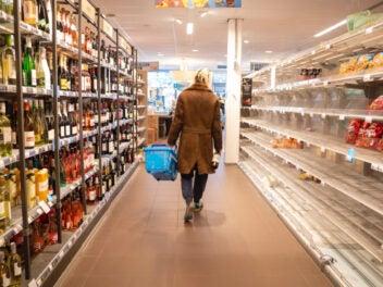 Eine Person zwischen zwei Einkaufsregalen