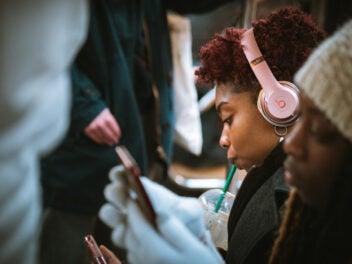 Eine Frau mit Kopfhörern trinkt aus einem Strohhalm Kaffee, streamt Musik und fährt U-Bahn