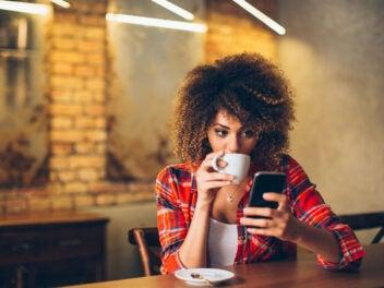 Frau trinkt Kaffee und schaut auf ihr Smartphone