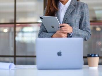 Eine Business-Frau hält ein iPad und blickt auf ein MacBook von Apple