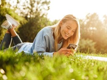 Frau liegt mit dem Handy im Gras