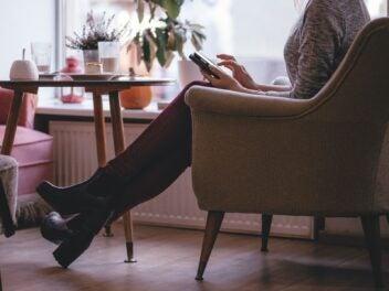 Eine Frau mit einem Handy im Sessel