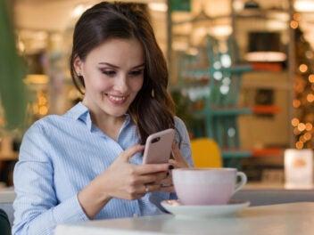 Frau mit Handy in der Hand und einem Kaffee