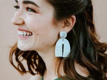 Lachende Frau mit braunem Haar und Pendelohrring im Profil