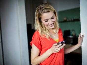 Frau mit Smartphone lacht