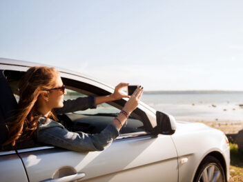 Frau fotografiert mit dem Smartphone aus dem Auto