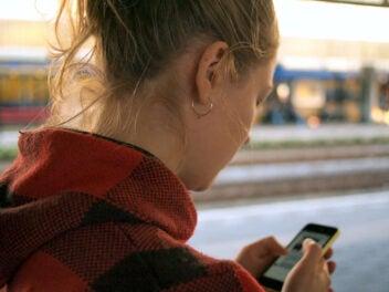 Frau mit Smartphone in der Hand nutzt mobiles Internet am Bahnhof.