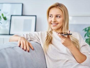 Frau nimmt Sprachnachricht mit einem Smartphone auf