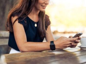 Eine Frau sitzt im Café und tippt auf ihrem Smartphone