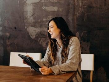 Eine lachende Frau sitzt mit einem Tablet in der Hand an einem braunen Tisch