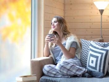 Frau mit Tasse Kaffee sitzend im Herbst zu Hause am Fenster
