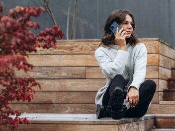 Eine Frau sitzt auf einerHolzstufe und telefoniert mit einem iPhone 13 Pro.