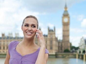 Eine Frau steht in London vor dem Tower of London und telefoniert mit dem Handy