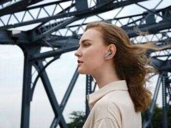 Eine Frau trägt Huawei Freebuds Kopfhörer unterwegs