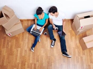 Frau und Mann mit Laptop, Tablet und Kaffee, umgeben von Umzugs-Kartons