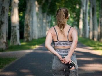 Frau in Sportklamotten wärmt sich fürs Joggen auf