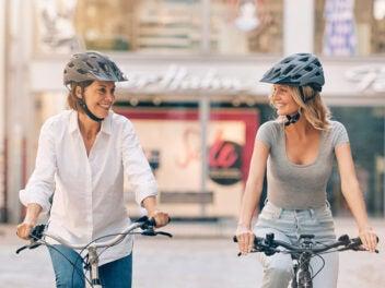 Zwei Frauen mit Helmen sitzen auf ihren Fahrrädern