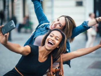 Frauen mit Smartphone machen Selfie