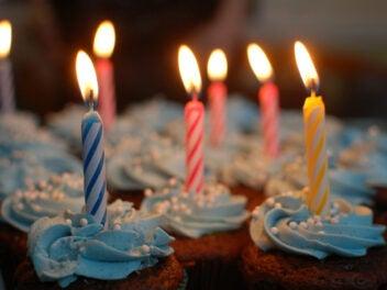 Muffins mit angezündeten Geburtstagskerzen.