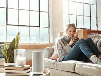 Eine Frau sitzt im Wohnzimmer auf der Couch, auf dem Couchtisch steht der Gigaset Smartspeaker L800HX