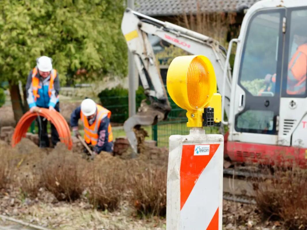 Arbeiter verlegen Glasfaser-Kabel in die Erde, ein Bagger wartet auf seinen Einsatz