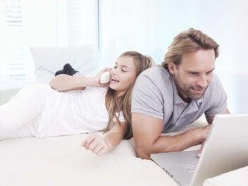 Vater und Tochter nutzen Notebook und Telefon