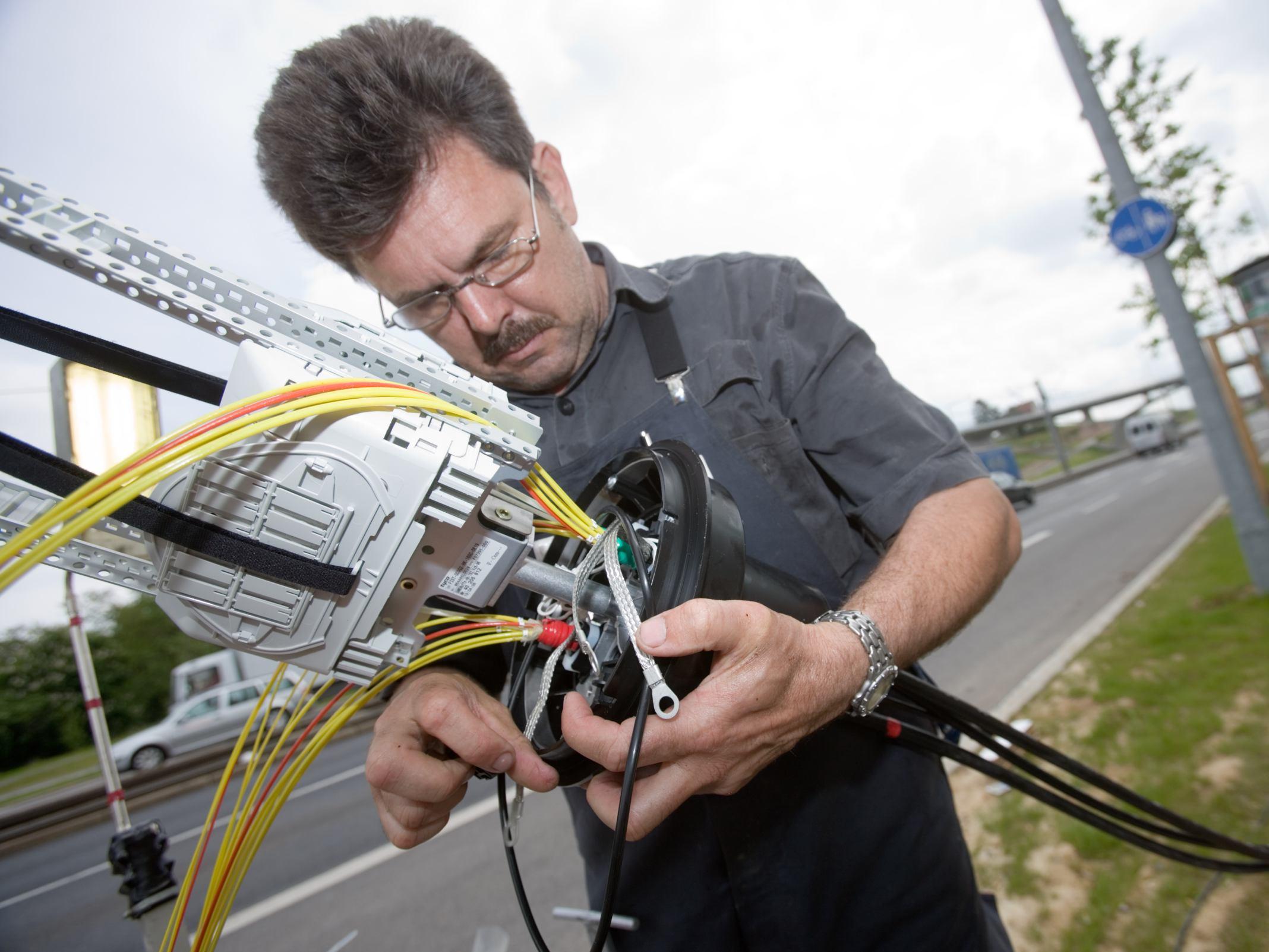 Ein Techniker arbeitet an einer Glasfaser-Muffe