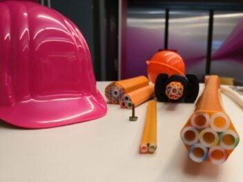 Ein Bauhelm und Glasfaser-Speedpipes liegen auf einem Tisch