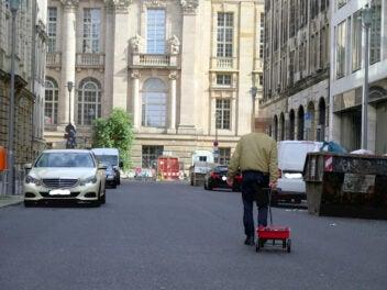 Google Maps reingelegt: Mann spaziert auf berliner Straße mit rotem Handkarren
