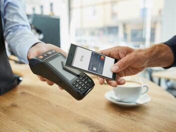 Ein Handy mit Google-Pay-App wird im Café an ein Kartenterminal gehalten