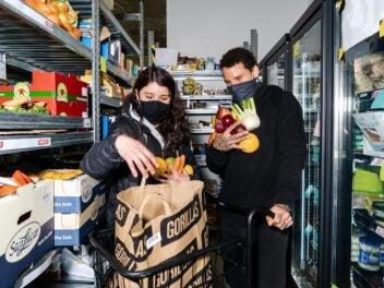 Zwei Mitarbeiter sammeln Lebensmittel ein und verpacken sie in eine Tüte