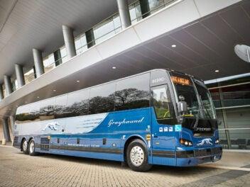 Greyhound Bus in den USA steht vor einem Stadion.