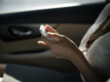Ein Handy in der Hand einer Frau im Auto