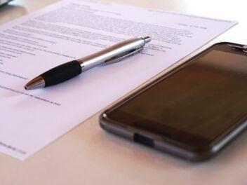Symbolbild Handyvertrag: Ein Handy, ein beschriebenes Blatt Papier und ein Stift liegen auf einem Tisch