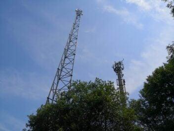Zwei Sendemasten mit Antennen in einem Waldgebiet