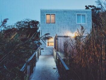 Ein eckiges Haus mit Holzaufgang zwischen Gräsern und Bäumen im Urlaub