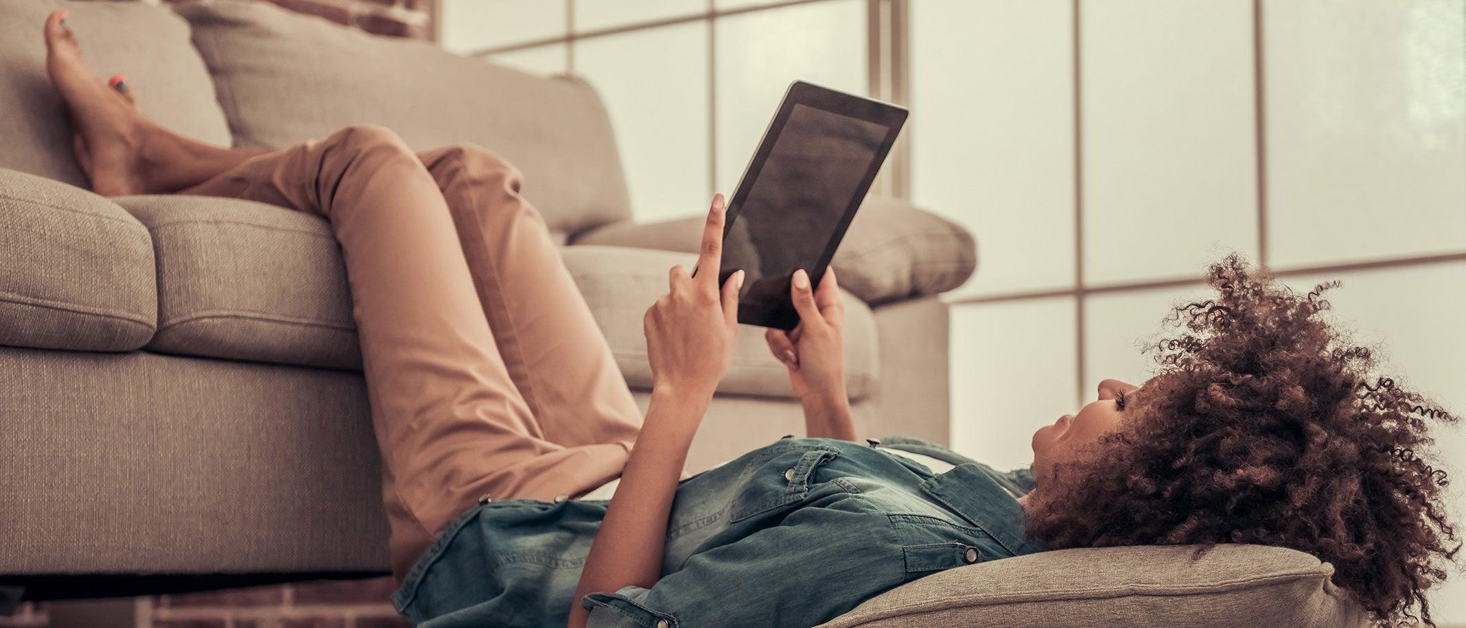 Frau surft zuhause mit dem Tablet