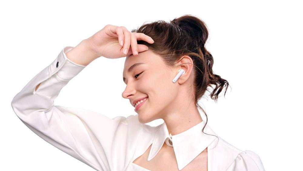 Huawei FreeBuds 4i im Ohr einer Frau.