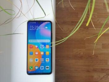 Das Huawei P smart 2021 mit aktivem Display auf einer weißen Fensterbank mit Holz und Pflanzen im Hintergrund