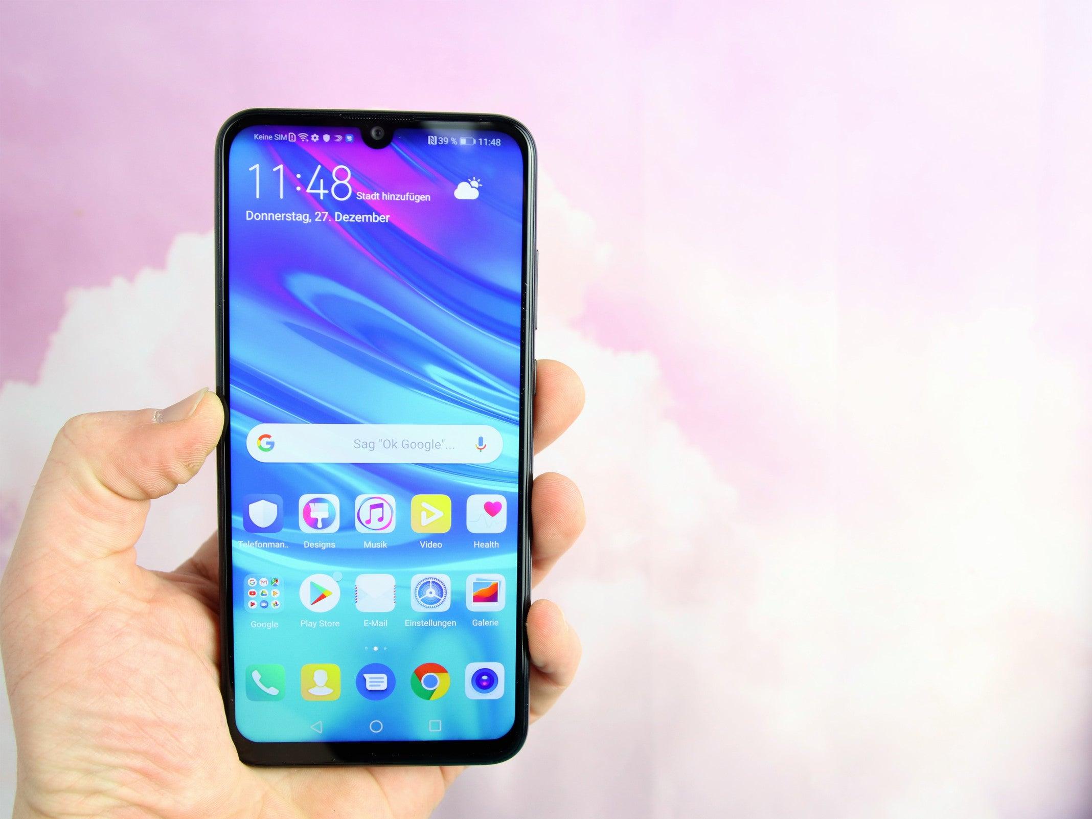 Huawei P smart 2019 in der Hand vor rosa Hintergrund