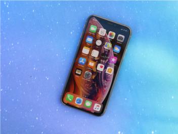 Das Apple iPhone XS mit eingeschaltetem Display vor blauem Hintergrund