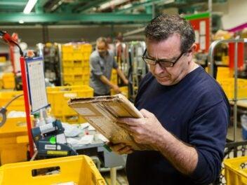 Ein Mann liest die Beschriftung eines Umschlags, im Hintergrund sind Behälter der Deutschen Post zu sehen