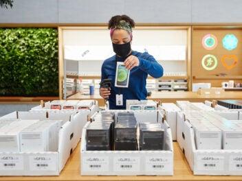 Verkäuferin mit iPhone 12 im Apple Store