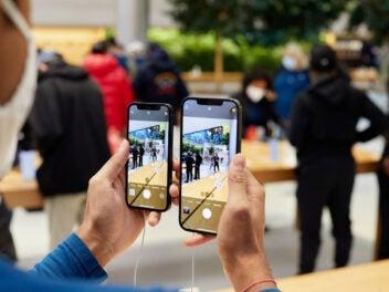 Ein Mann hält iPhone 12 Pro Max und iPhone 12 Mini zum Vergleich in der Hand