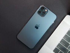 iPhone 12 Pro in Blau neben einem MacBook