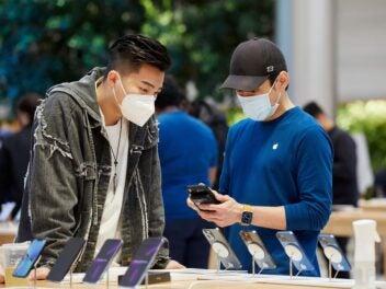 Symbolbild iPhone 13 mit zwei Personen im Apple Store