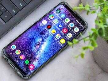 Ein iPhone mit aktivem Display neben Pflanzen und einer Tastatur auf einem weißen Tisch