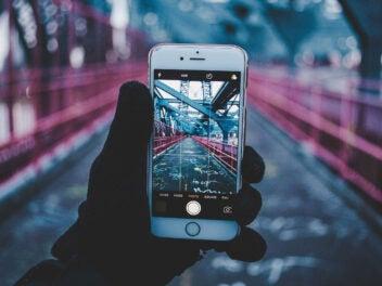 iPhone auf einer Brücke mit Telekom-Magenta-Farben